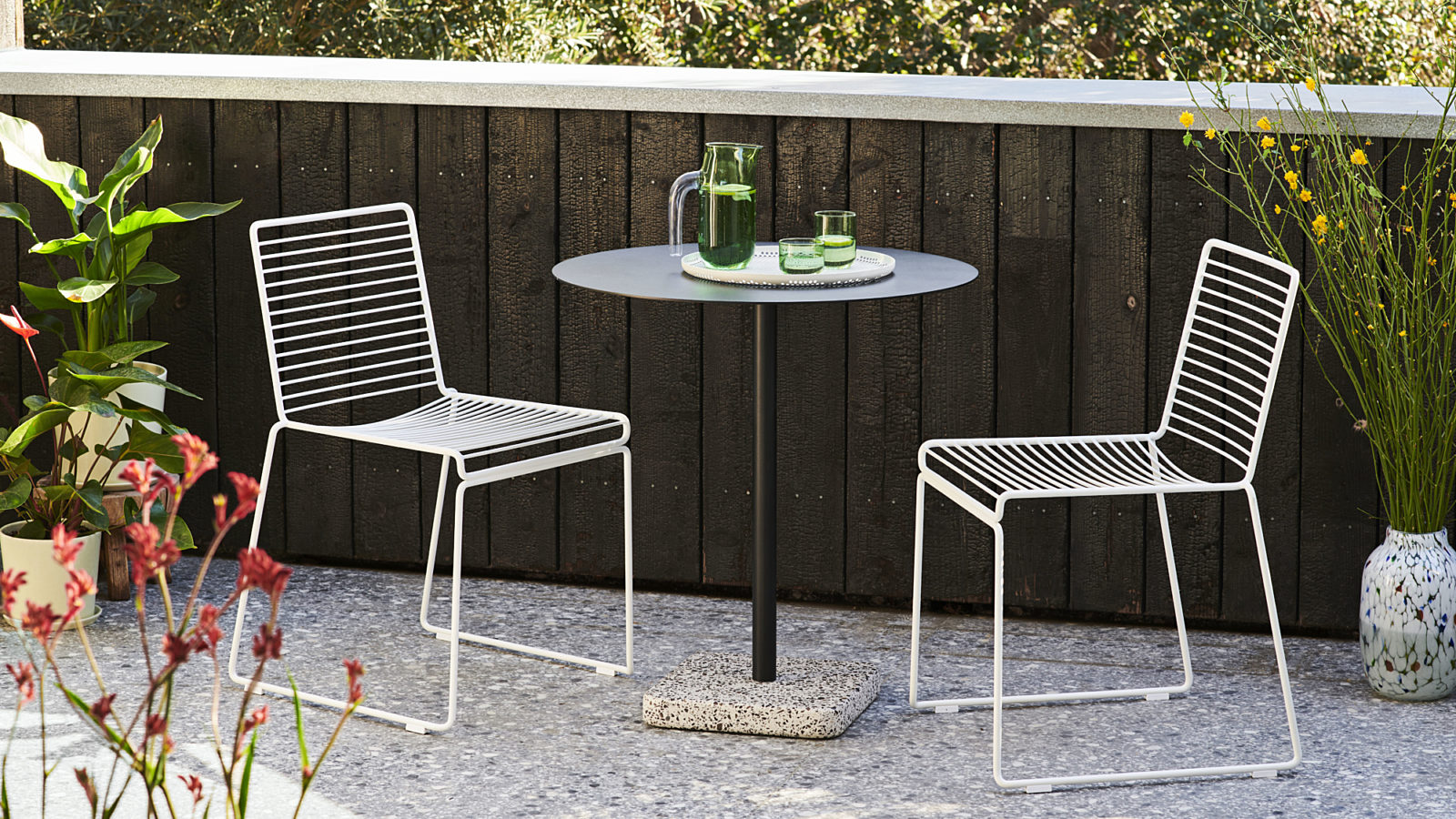 Two white HAY Hee Dining Chairs facing each other across a black round HAY Terrazzo Table on a stone patio outside.