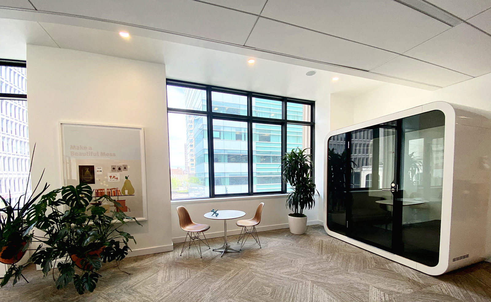 A white Framery Q on the second floor of our headquarters next to two wood Eames Side Chairs and a white Eames table.