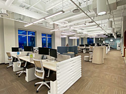 Rows of white workstations that each have a task chair and two Flo Monitor Arms holding screens.