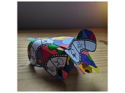 Three images of a three dimensional paper elephant decorated in with bright colored patterns and hand-drawn images of Eames chairs.