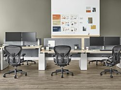 An image of three Renew Link Workstations with Dual Flo Monitor Arms holding screens and graphite Aeron Task Chairs.