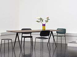 An office with black HAY Soft Edge 10 chairs arranged around a wood Pyramid Table holding a vase of flowers.