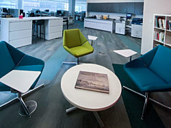 A photo of two blue and one green lounge chair with attached tablet arms surrounding a low white coffee table.