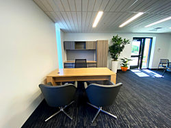 An executive office with a task chair behind a wood desk facing two grey lounge chairs with plants and another table in the background.