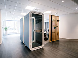 The interior of an office with two blue Framery O pods arranged next to each other to be used for private conversations.