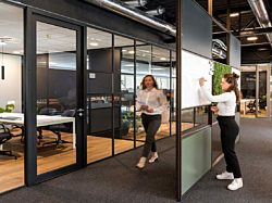 An office interior with a Maars M923. partition wall with a woman writing on the integrated whiteboard.