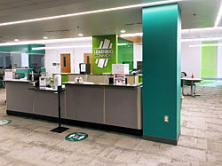 A photo of the lobby of the Delta College Saginaw Center with a grey welcome desk with a hand sanitizer stand and signage about social distancing in front.