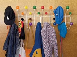 Two multicolored Eames Hang-it-Alls hung next to each other on a wall holding hats, coats, and bags.