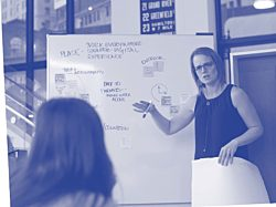 A woman standing and speaking in front of a whiteboard filled with writing at the MarxModa Detroit headquarters.