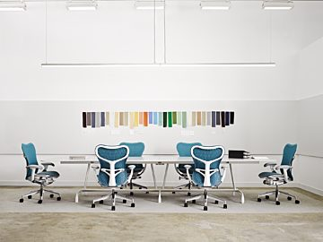 A conference room with a long white table surrounded by blue and white Mirra 2 chairs with a colorful art installation on the wall behind the table.