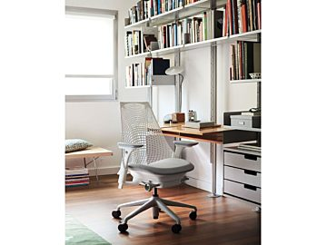 A home office with a white and grey Sayl Task Chair in front of a desk surrounded by bookshelves.