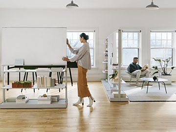 A woman pushes an OE1 Agile Wall with an integrated whiteboard above two storage shelves across the office.
