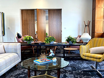 Geiger chairs and sofa facing each other with a glass top table in between them in the fourth floor family room at MarxModa headquarters in Detroit.