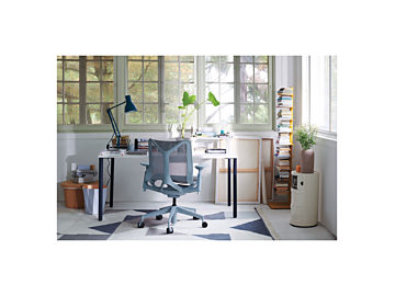 A home office with a blue Cosm Task Chair in front of a OE1 table with a white top and navy legs surrounded by plants, a bookshelf, and storage.