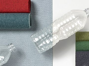 An image of two empty clear plastic bottles on top of fabric swatches from Herman Miller's Revenio Textile Collection.