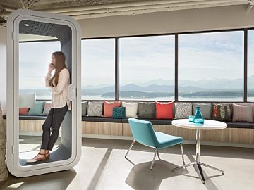 A woman on the phone in a white Framery O in an office next to a lounge chair and side table.