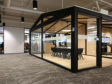 A conference room enclosed in metal and glass DIRTT partition walls in the middle of an office.