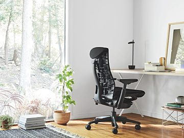 A photo of a black Embody chair in a home office in front of a white desk with a task lamp on it.