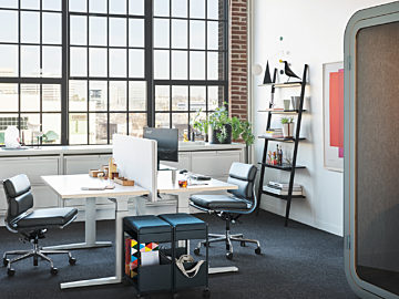 Two white sit-to-stand desks arranged back to back with black Eames Softpad Chairs next to a Framery O.