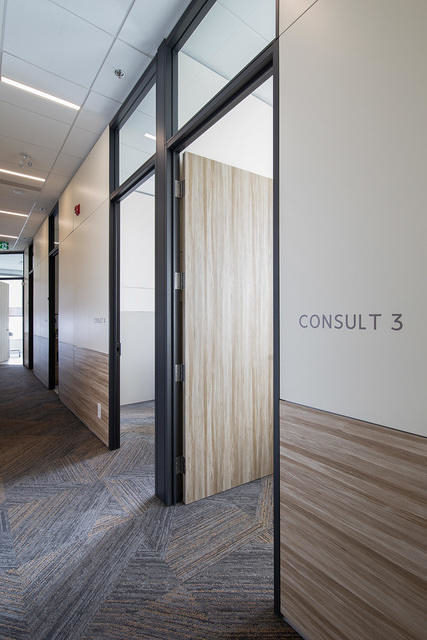 A hallway with patient rooms created used DIRTT prefabricated interior construction.