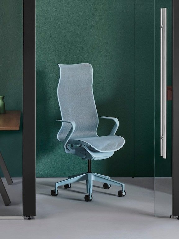 A high-back light blue Cosm task chair in a small glass-enclosed room in an office with green walls.