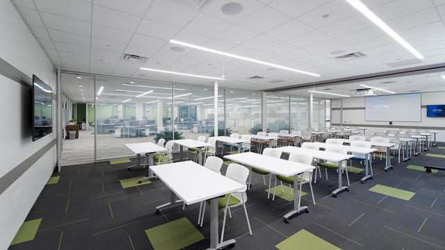 A training room with rows of white flip-top tables and white and green caper chairs facing a large television screen.