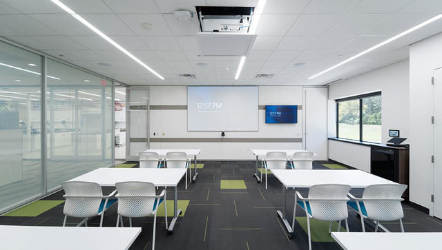 A training room with a DIRTT glass and metal partition wall along the left side.