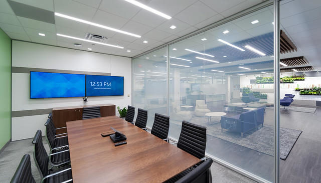 A meeting room with a DIRTT glass partition wall separating it from a lobby.
