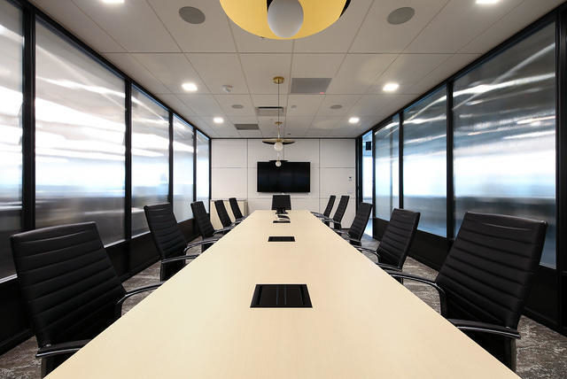A conference room lined two sides with glass and metal walls and doors.