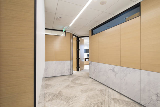 A hallway lined with wood panels constructed using DIRTT prefabricated solutions.