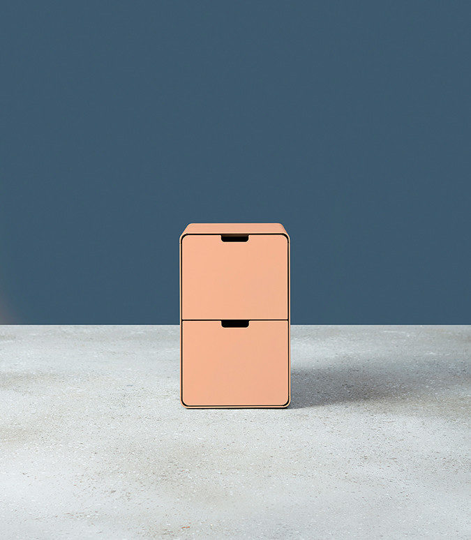 A pink Montisa Russ storage pedestal on a grey floor with a navy background.