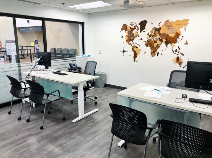 Two workstations with white sit to stand desks, Verus Task Chairs, Caper Guest Chairs, and monitors on Flo Monitor Arms.