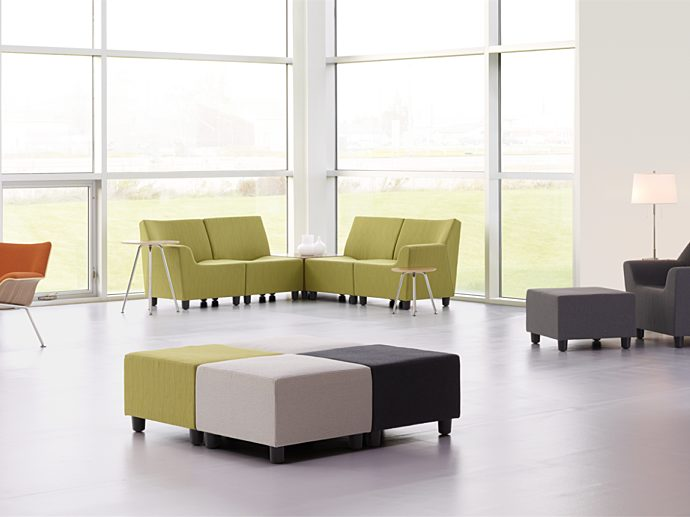 A lobby with orange Swoop Plywood Lounge Chairs, green Swoop modular sofas, a blue Swoop Lounge Chair and Ottoman, and multicolored square Swoop Ottomans.