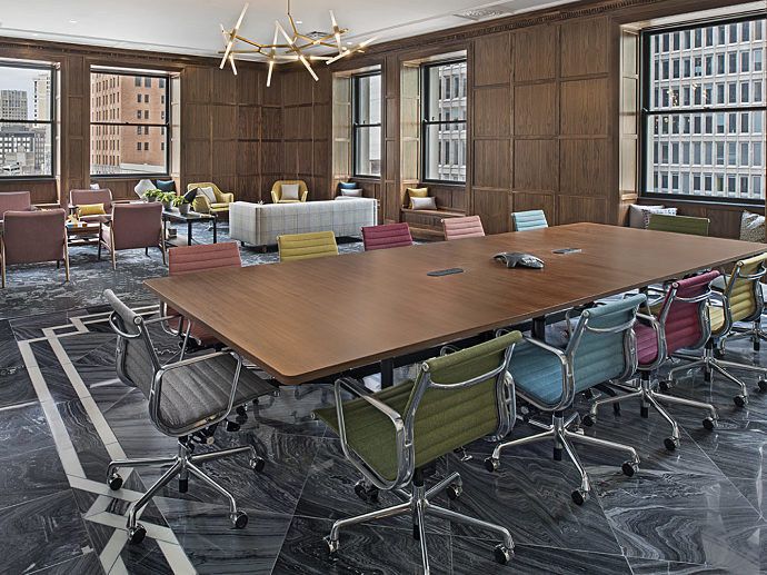 The fourth floor conference room of MarxModa's downtown headquarters with wood-paneled walls, marble floors, a long wooden conference table.