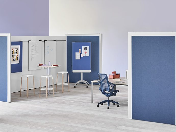 An image of an office with tall blue boundary panels and a high-back blue Cosm.