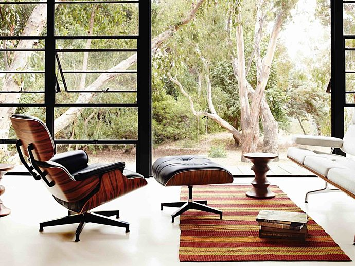 A white Eames Sofa and black Eames Lounge and Ottoman in a light-filled living room with two Eames Walnut Stools.