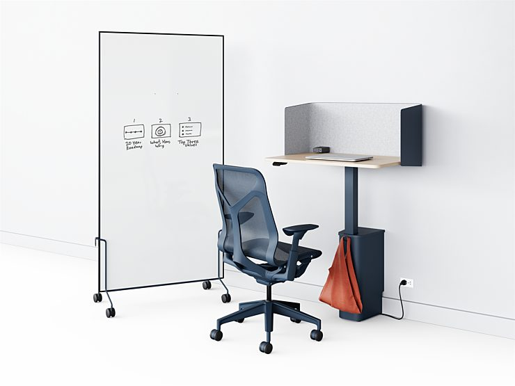 A navy OE1 Micro Pack plugged into a wall in front of a navy Cosm task chair with a OE1 Mobile Whiteboard next to it to create a private workspace.