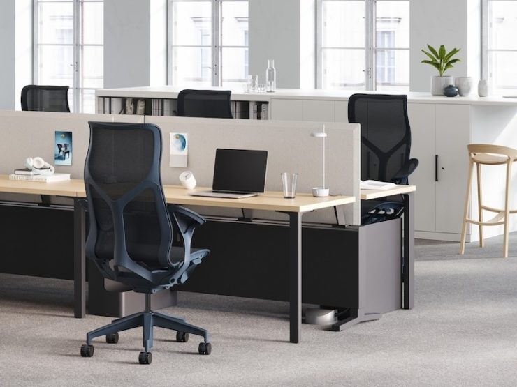 Rows of workstations with dark blue high-back Cosm task chairs, light grey privacy panels, and task lights.