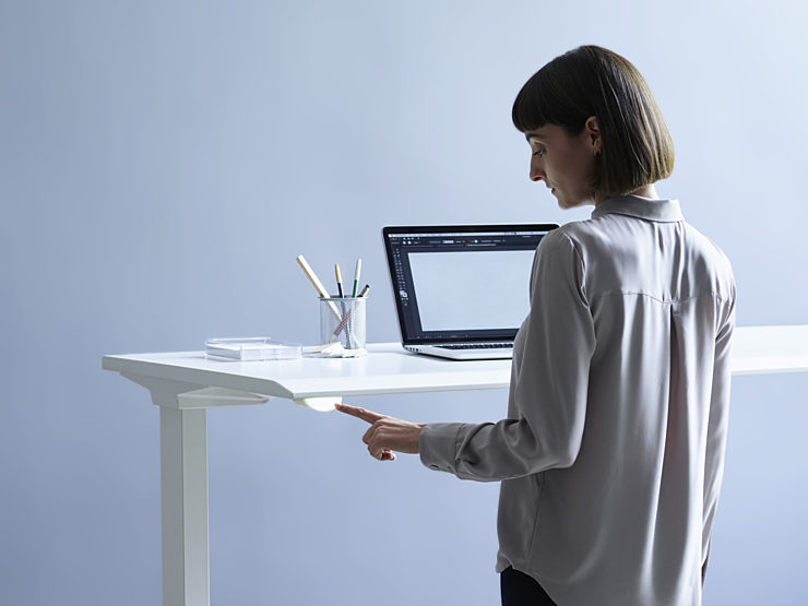 A woman reserving a sit-to-stand desk using Live Platform.