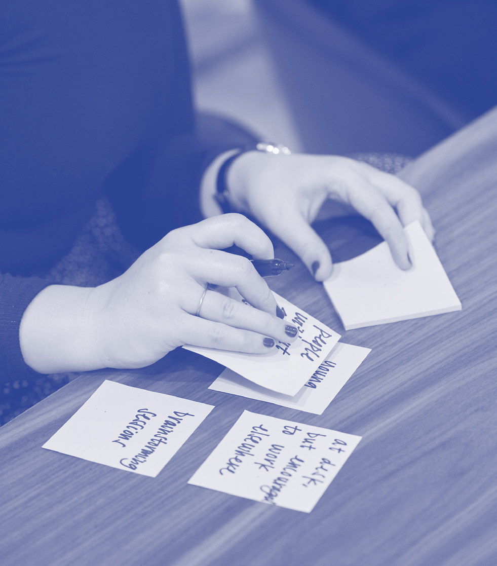 Hands arranging sticky notes on a table with ideas written on them.