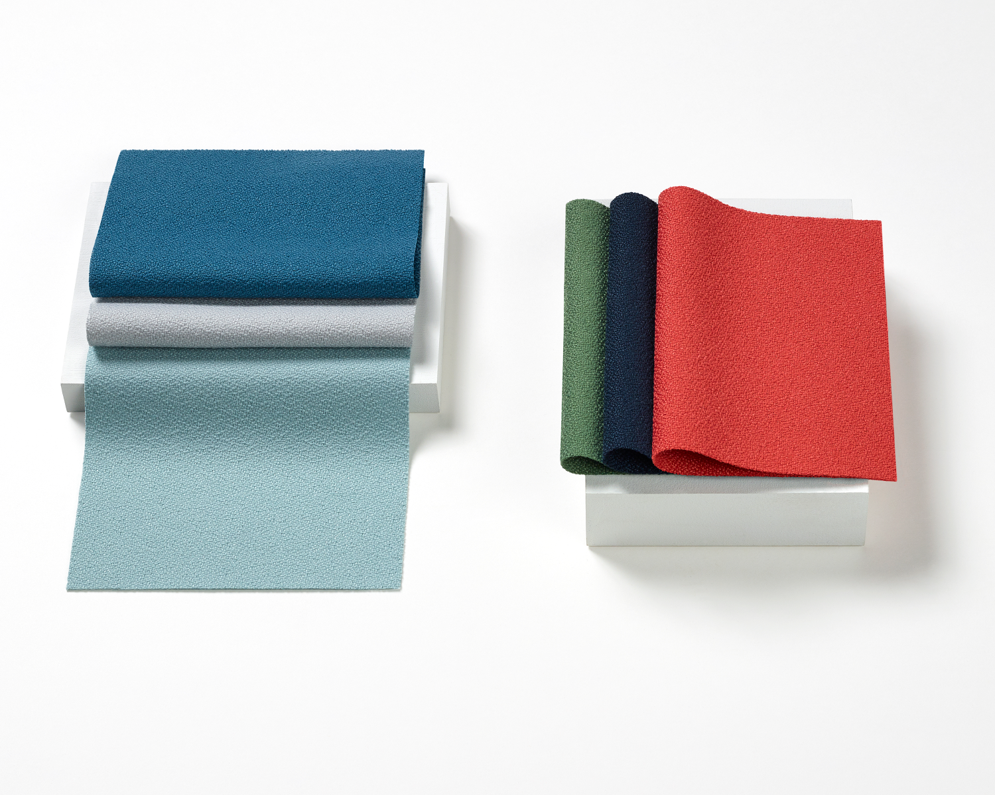An image of Crepe fabric swatches on a white surface. Colors include blues, red, green, and grey.