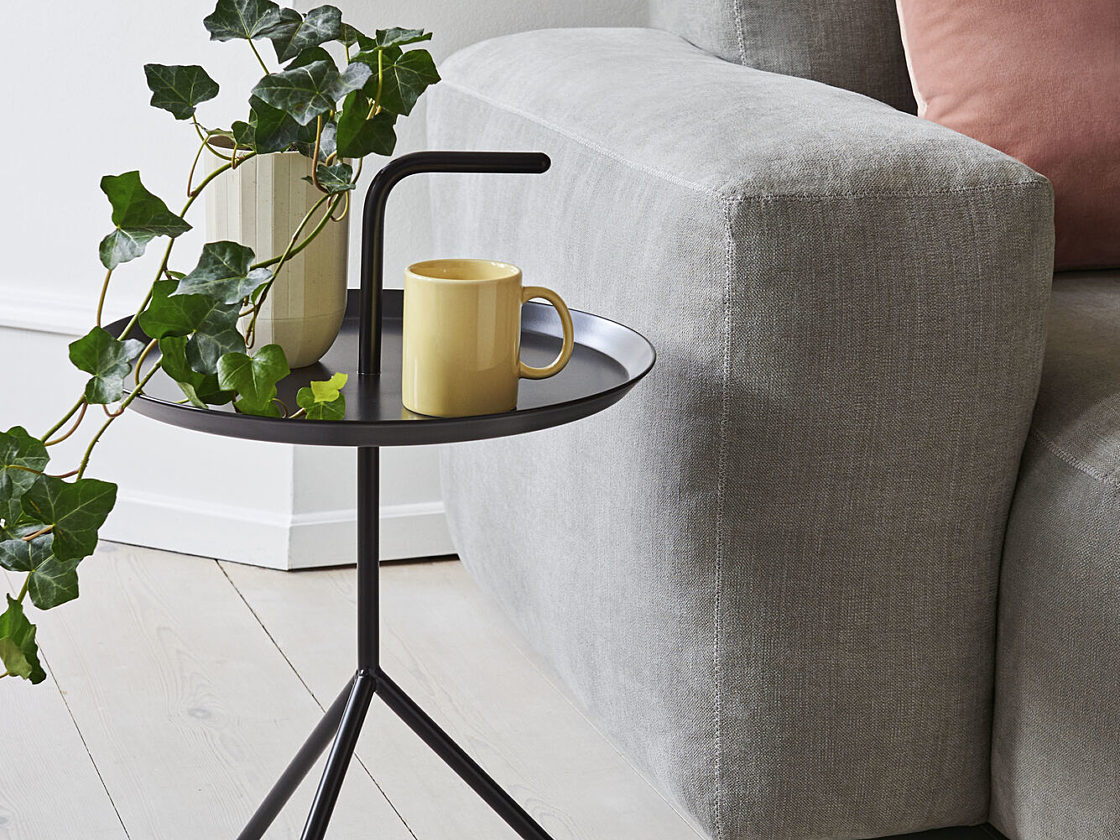 A black HAY Don't Leave Me Side Table holding books and a coffee mug next to a sofa.