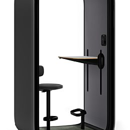 A Framery One with a black shell and grey interior with an integrated stool and height-adjustable desk on a white background.