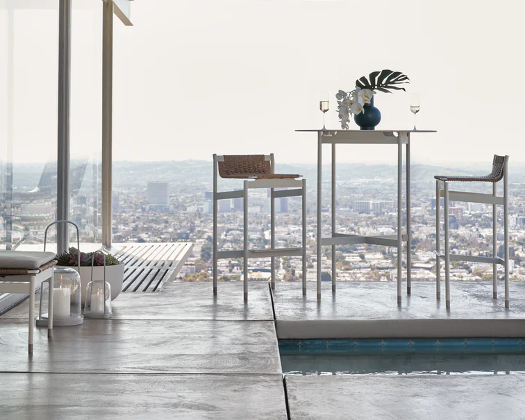 Two white Sommer Barstool facing eachother across a white metal table sitting on a deck overlooking a large cityscape.