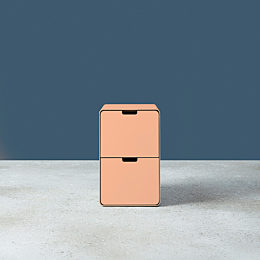 A light pink Montisa Russ storage pedestal on a grey floor with a navy background.