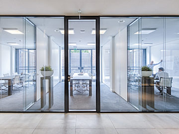 An image of a hallway lined with Panorama Slim partition glass and steel walls with offices and a conference room behind them.