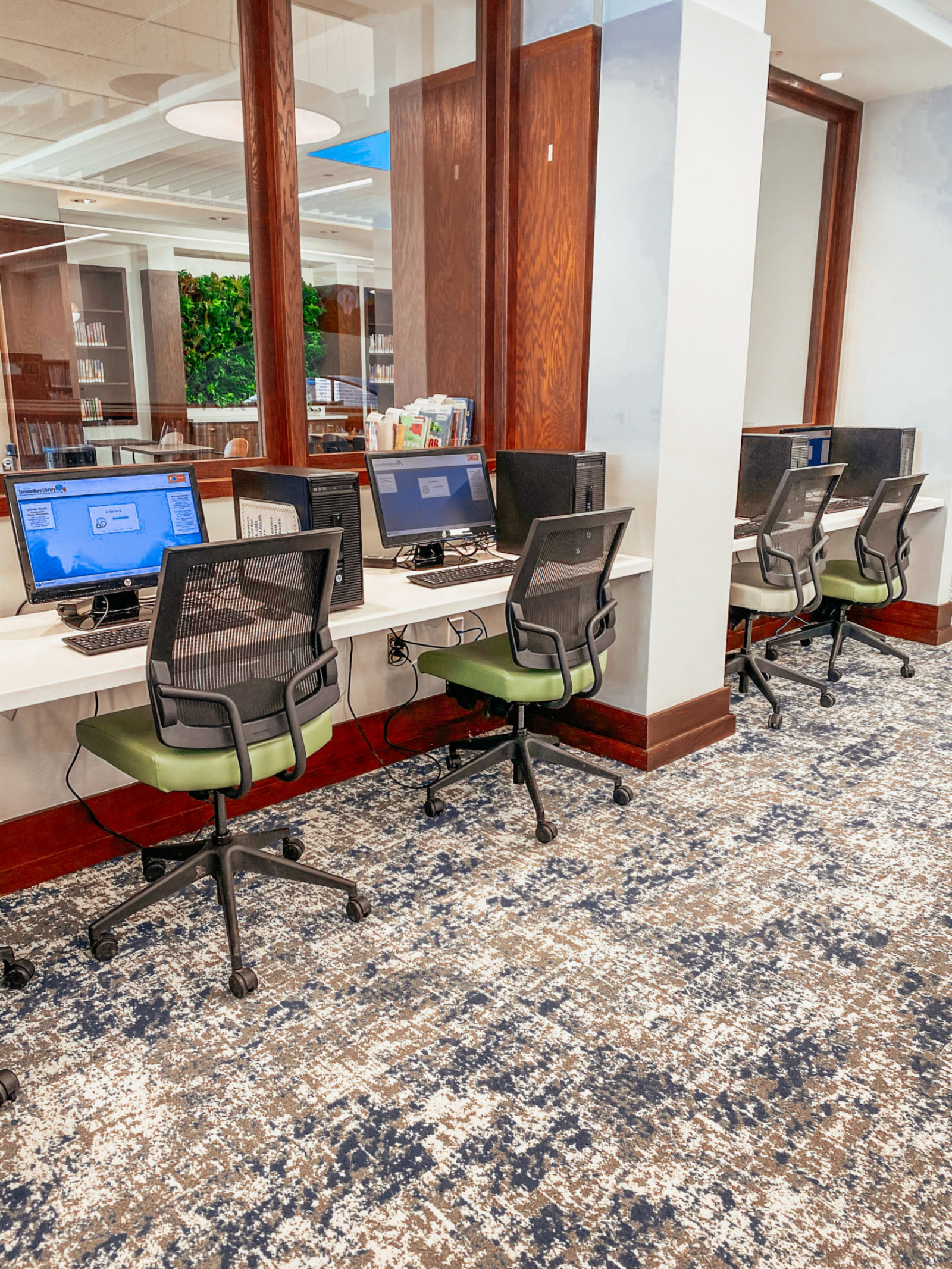 An image of the computer stations in the children's section with black task chairs that have green seats lined up in front of a ledge with computers.