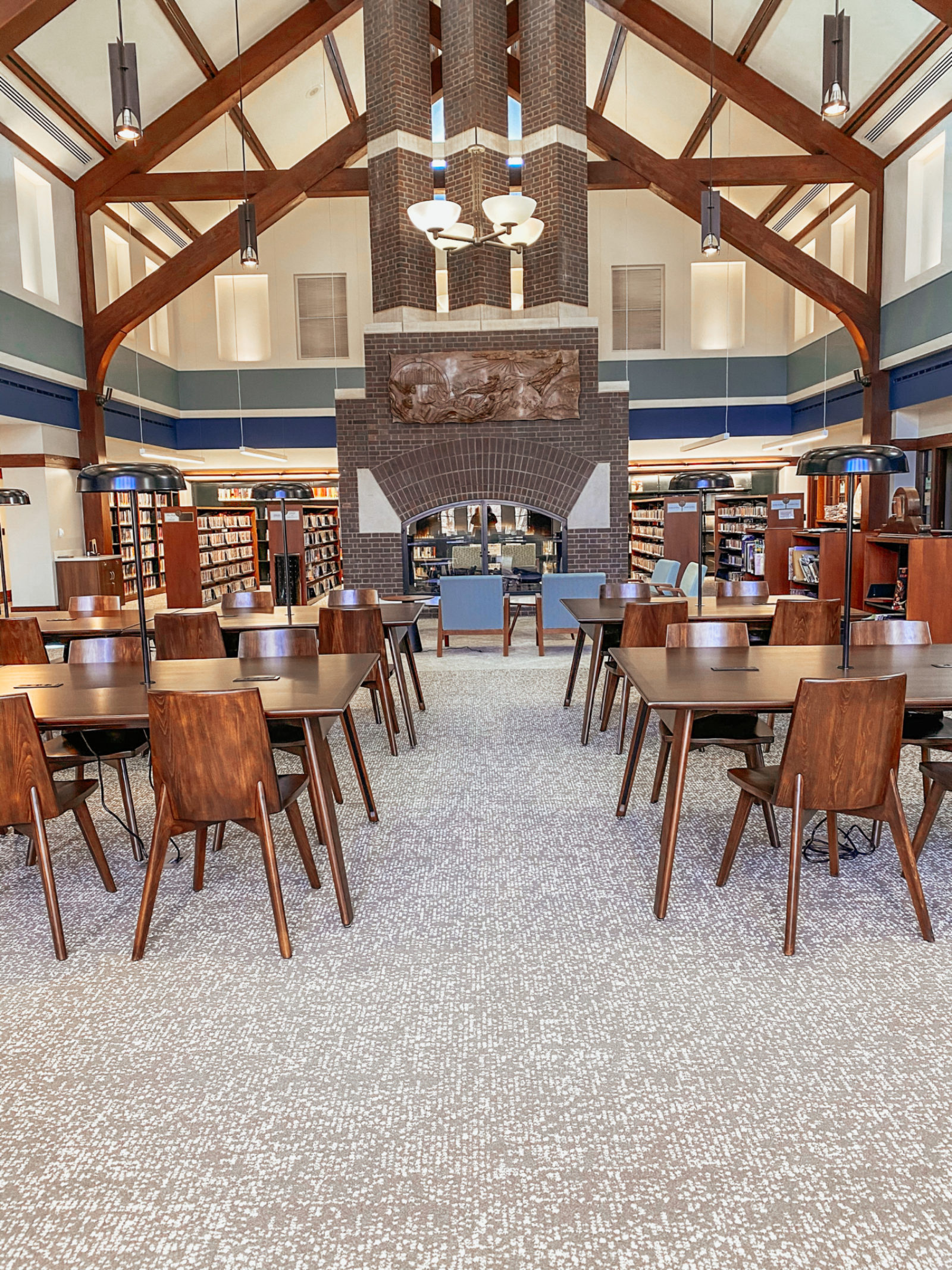 An image of the center of the library with a view of the study tables and chairs and the central lounge area with blue chairs and wood coffee tables.