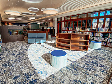 An image of the children's section with custom wood bookcases, blue ottomans, blue sofas, and artistic circular overhead lighting.